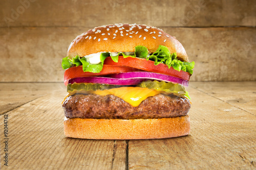 Fotografie, Obraz  Single solo burger hamburger cheeseburger on table wooden surface delicious perf
