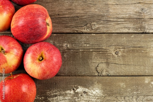 Foto  Freshly harvested apples, side border on rustic aged wood background