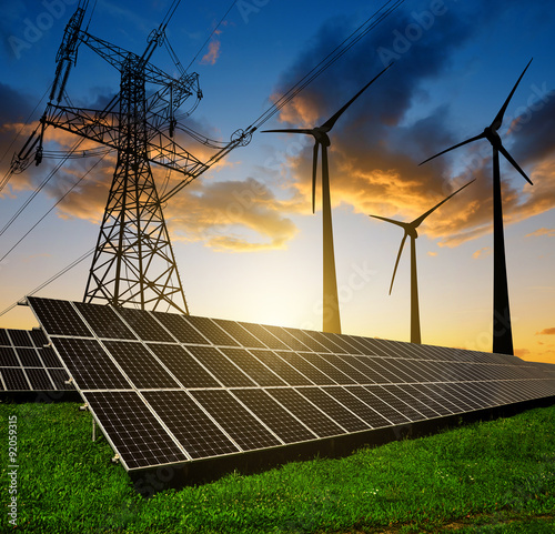 Photographie Solar panels with wind turbines and electricity pylon at sunset.