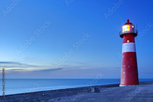 Photo Stands Lighthouse Red and white lighthouse and a clear sky at dusk