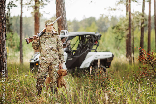 Foto op Aluminium Jacht Hunter with Rifle and Four Wheeler Tire in forest