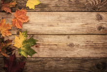 Autumnal Maple Leaves On The Wooden Table With Film Filter Effect Background