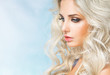 Leinwanddruck Bild - Beautiful woman - blonde, close-up on a blue background, looked down