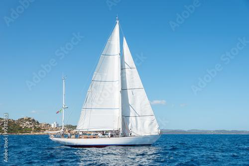 Fotografia  Elegant old italian style sailboat, on a wonderful blue sea, Sardinia, Italy