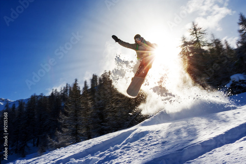 Tuinposter Wintersporten Powerful image of a snowboarder jumping over a kicker in the backcountry powder