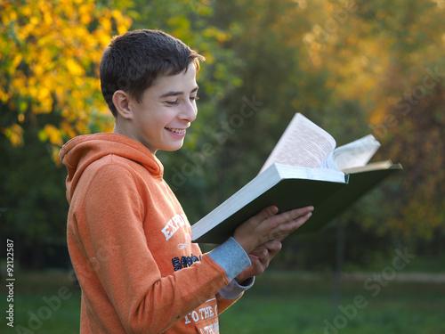 Deurstickers Мальчик читает книгу и улыбается. Осень, парк, солнце. Хорошее настроение, теплая погода. Позитивная фотография
