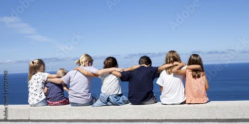 Fotografía  Niños cogidos por los hombros mirando el mar