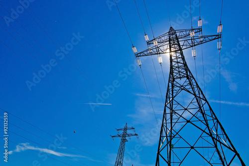 Fotografia Strommast mit Sonne vor blauem Himmel