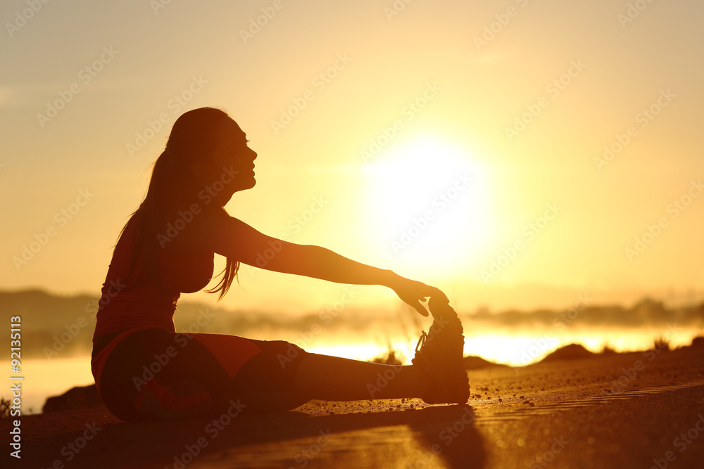 Fototapety, obrazy: Silhouette of a fitness woman stretching at sunset