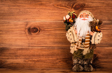 Santa-Claus Toy At The Wooden Background.