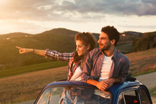 A Loving Couple, On A Summer Afternoon, Watching Sunset From The Roof Of An Old Car, Around The Classical Landscape Of Tuscany, Vineyards And Farmland. Woman Points To Look At A Point To Her Boyfriend