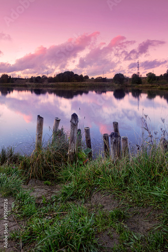 Tuinposter Purper Beautiful pink sunset on the river front with aura panorama