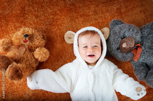 Little baby in bear costume with plush toys Poster