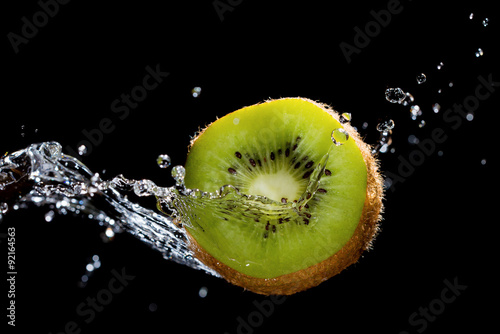 Fotografie, Tablou  Kiwi in water splash on black background