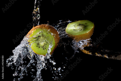Kiwi slices with clear water splash on black background