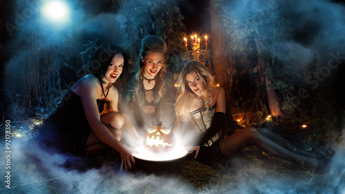 Fotografie, Obraz  Three beautiful witches are making magic. Dark forest on the bac