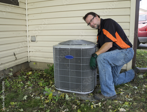 Fotografia, Obraz  Repairman Cleaning Outside Air Conditioner Unit Grill