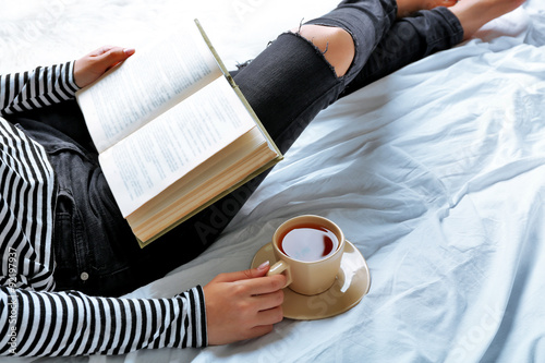 Deurstickers Ontspanning Woman on the bed with old book and cup of coffee, top view point