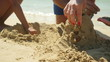 Family playing on the beach building sand castle. 4K UHD.