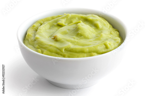 Fotografía  Round white bowl of tortilla guacamole dip isolated in perspecti