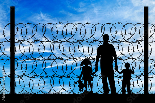 Fototapeta Silhouette of a family with children refugees