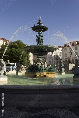 Papiers peints Fontaine Monumental fountain in Rossio Square in Lisbon, with few people around and a bus in the background
