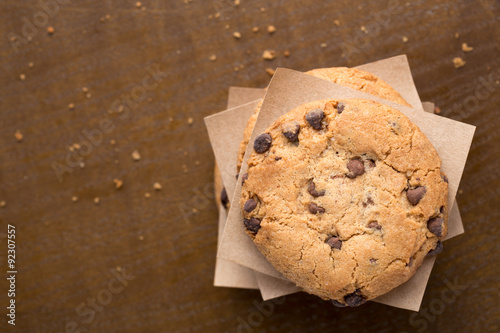 Foto op Plexiglas Koekjes Stacked chocolate chip cookies on brown wooden table