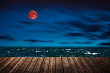Red Full Moon In Red Color Also Called Bloodmoon On The Background Sea.