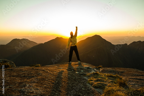 Fotografiet  Man celebrating success on top of a mountain