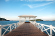 Beautiful white wooden bridge laying toward the sea with blue sky at the beach in Thailand.