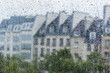 PARIS, FRANCE, on AUGUST 27, 2015. A fragment of skyline of the square in front of the Centre Georges Pompidou, a look through a wet window. It is raining, water drops on glass, focus on drops