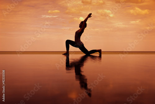 silhouette Reflextion of low lunge in Yoga pose with sunset background Wallpaper Mural