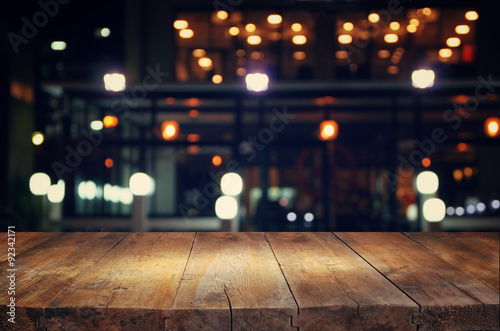 image of wooden table in front of abstract blurred background of resturant light Fotobehang