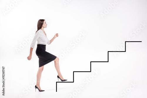 Obraz na płótnie Young businesswoman walking up on stairs