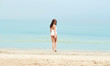 young woman in swimsuit walking on beach