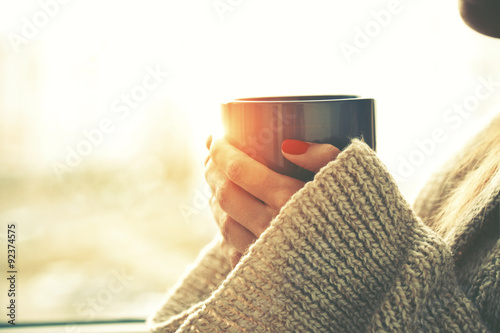 Spoed Foto op Canvas Thee hands holding hot cup of coffee or tea in morning sunlight
