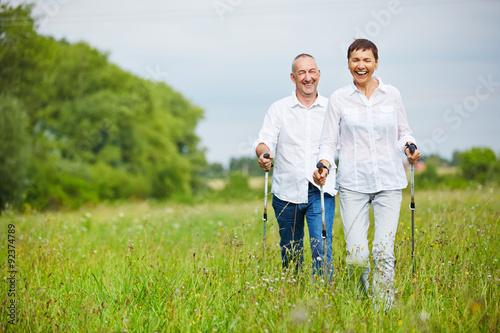 Frau und Mann wandern über Feld im Sommer Poster