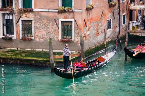 Türaufkleber Gondeln man in gondola in narrow canal with bridge Venice, Italy, Europe