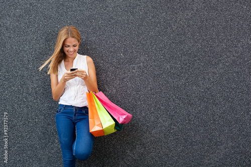 Fotografía  Happy young woman typing a message the phone after shopping