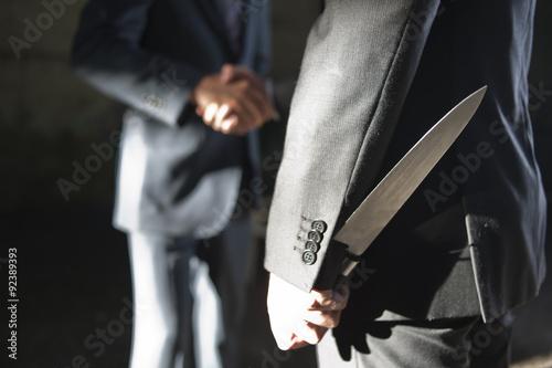 Vászonkép Dos hombres de negocios parecen hacer tratos mientrras esconden cuchillos
