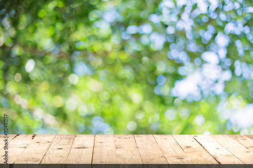 Bois wood table perspective and green leaf bokeh blurred for natural