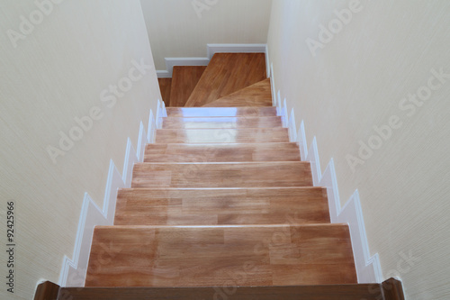 Tuinposter Trappen The light that shines through the window of a wooden staircase