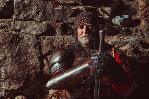 Fotografie, Obraz  Staré středověké Král v brnění s mečem na skalách pozadí