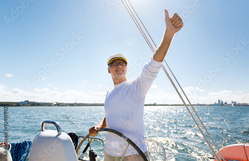 In de dag Schip senior man at helm on boat or yacht sailing in sea