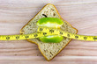 Apple on top of bread wrapped with measuring tape on wooden surface. Healthy diet concept. Selective focus.