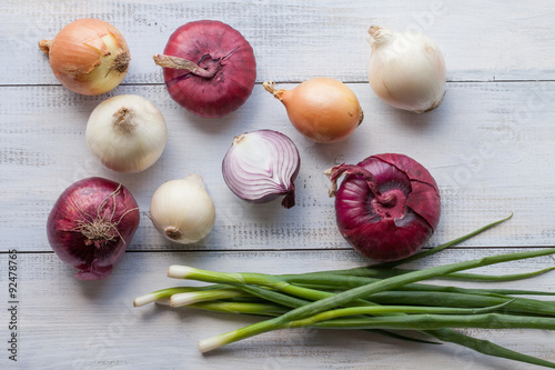 Fotografía  Assorted farm fresh onions on a wooden table with spring onions