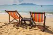 sun beach chairs on shore near sea.
