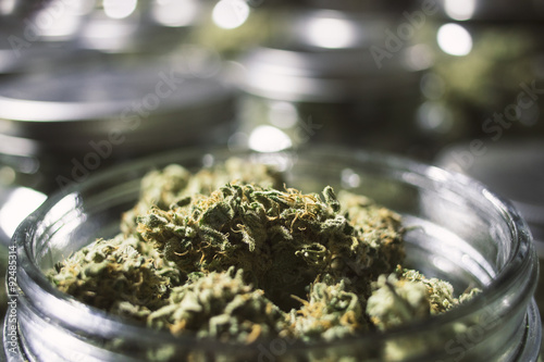 Photo  Close Up Marijuana Buds in Glass Jar with Blurry Background