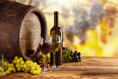 Poster Chocoladebruin Red and white wine bottle and glass on wodden keg
