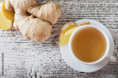 Photo sur Toile The Ginger tea in a white cup on wooden background